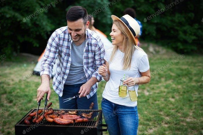 Junges weibliches und männliches Paar Backen Grill in der Natur