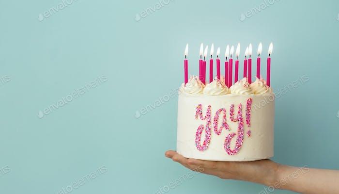 Hand holding birthday cake
