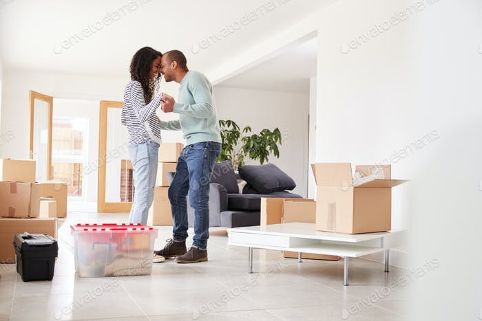 Loving Couple Surrounded By Boxes In New Home On Moving Day