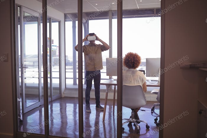 Female colleague with businessman wearing VR headset in office