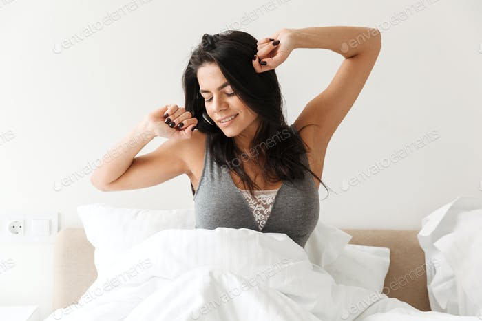 Portrait of gorgeous woman stretching after sleep, while resting