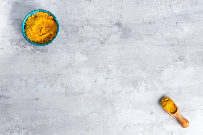 Turmeric Curcuma powder pile isolated on stone background, top view