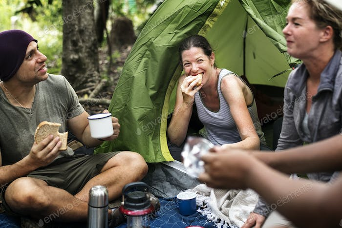 Group of diverse friends camping in the forest