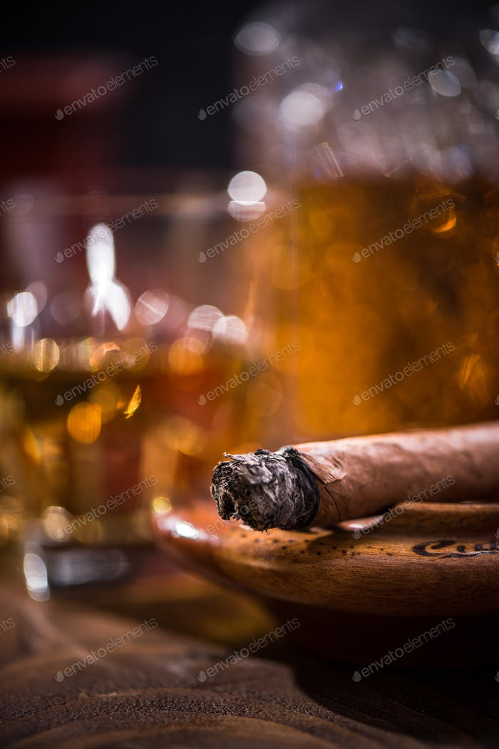 Cuban cigar smoking in wooden ashtray