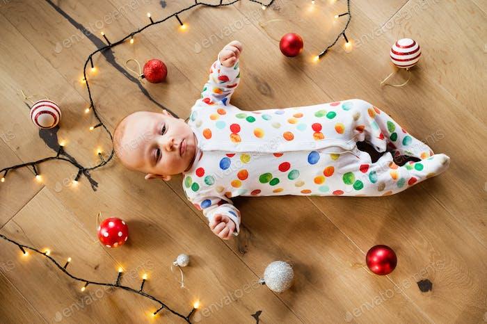 Kleiner Junge auf dem Boden zur Weihnachtszeit.