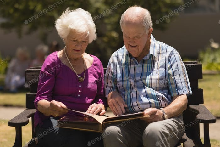 Active senior couple concentrated looking at photo album while sitting on a benchin the park