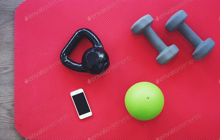 Gym equipment on red mat background, top view