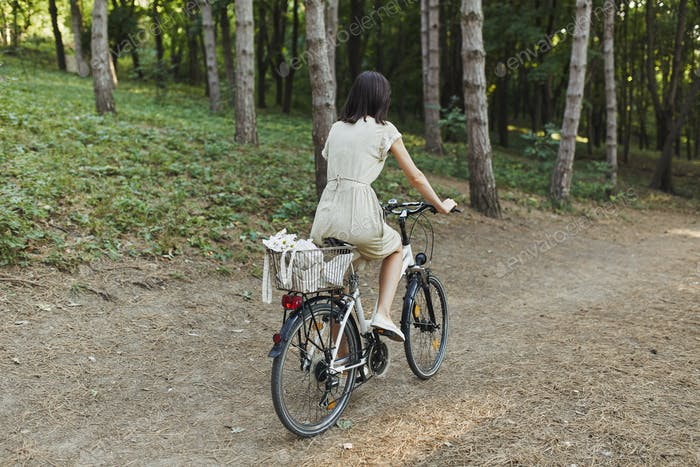 Outdoor portrait of attractive young brunette on a bicycle.