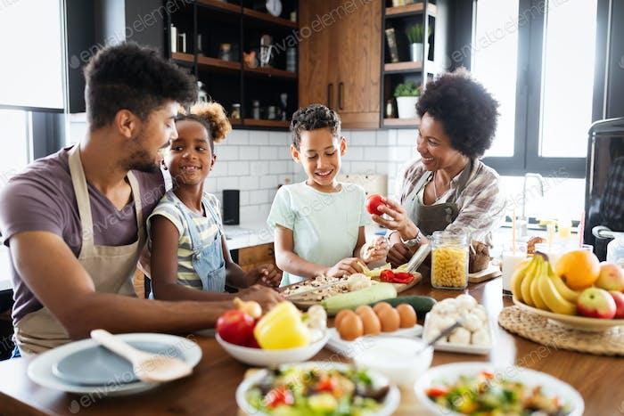 Fröhliche afrikanische Familie, die gesunde Ernährung zusammen in der Küche