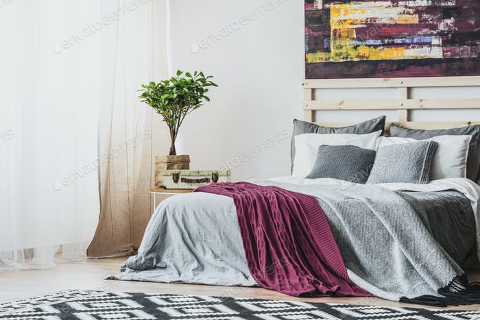 Purple blanket on grey bed and patterned carpet in bedroom inter