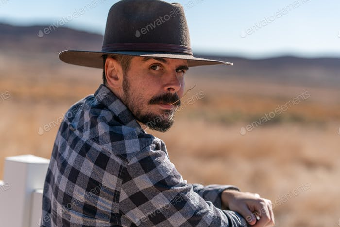 Cowboy with grey hat, moustache and checked shirt