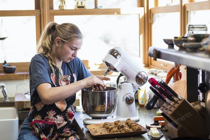 Dreizehn Jahre altes Teenager-Mädchen mit Mixer in der Küche.