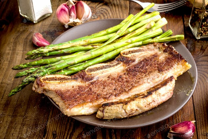 grilled barbecue steak with green asparagus, on rustic wood