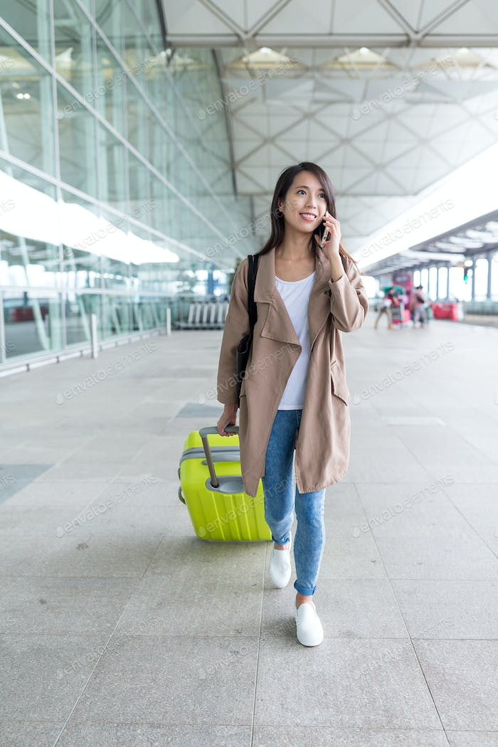 Young woman go travel with her luggage and talk to cellphone