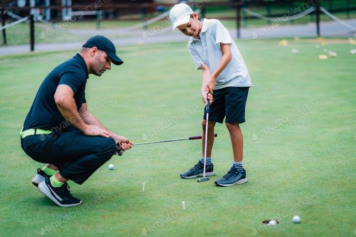 Golf lernen. Junge Üben Putting mit Instruktor