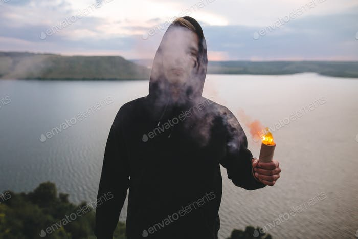 Ultras hooligan holding flare torch with burning fire in hand while standing on  view on river