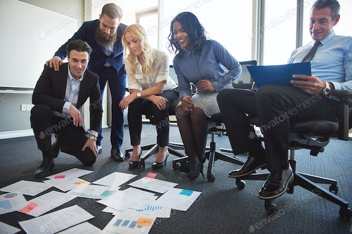 Businesspeople discussing paperwork laid out on an office floor