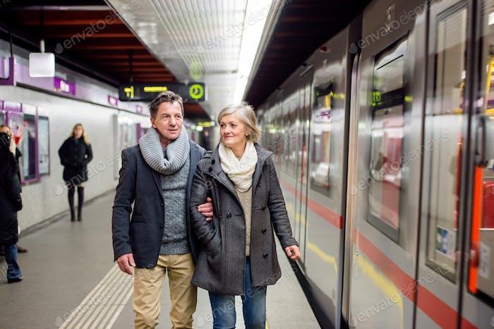 Senior couple at the underground platform, waiting