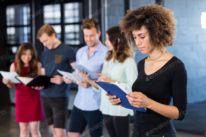 Frau Blick auf Zwischenablage während ihre Kollegen stehen hinter ihr im Büro