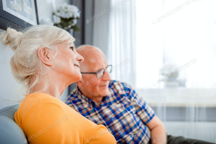 Senior couple at home spending time together watching tv