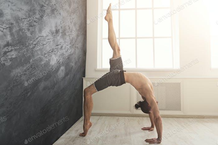 Young man practicing yoga at wall