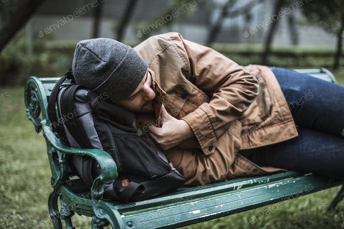 Homeless Adult Man Sleeping on Bench in The Park
