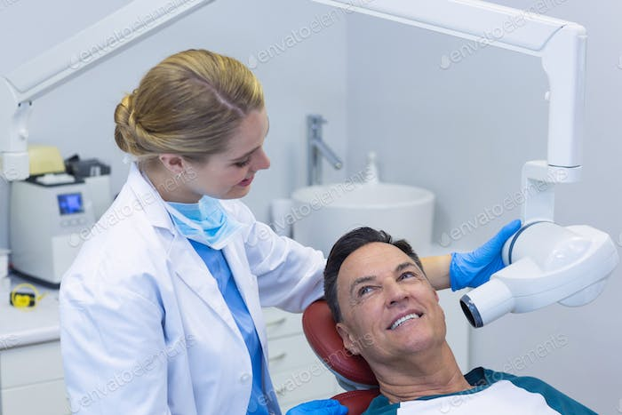 Dentist examining a male patient with dental tool