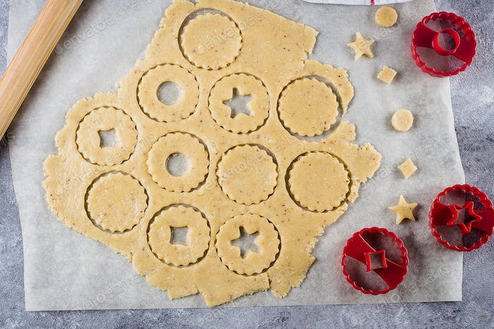Process traditional Christmas Linzer cookies. Raw dough and cutters for the holiday cookies on table