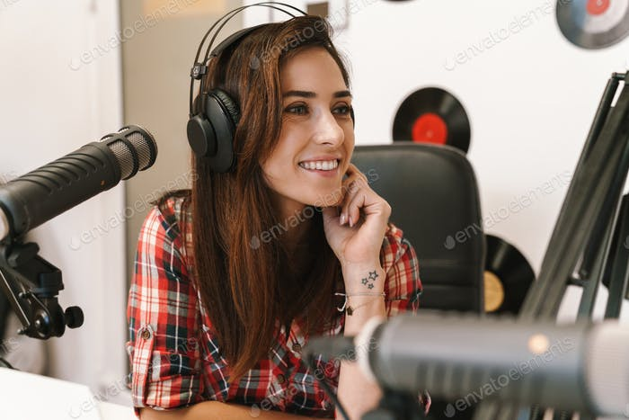 Image of young happy dj woman wearing headphones working at radio station