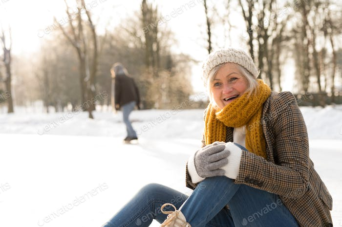 Senior woman with husband in winter nature ice skating.