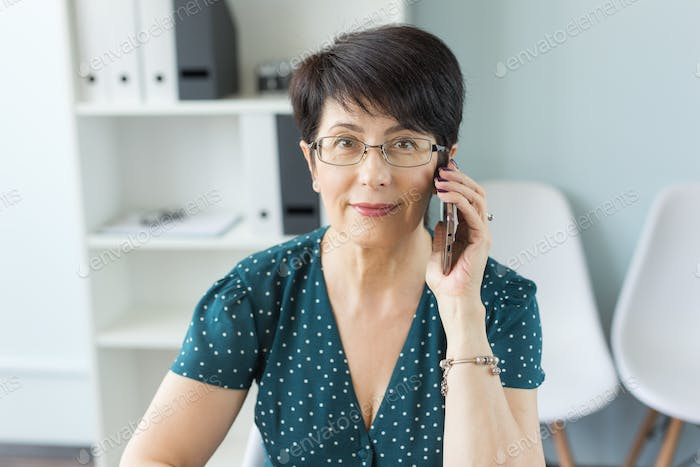 People, technology and communication concept - Adult business lady talking by phone in office