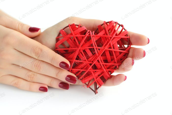 Wicker red heart in woman's hands on white background. Closeup h