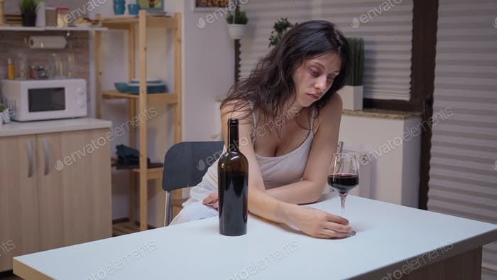 Depressed woman drinking alone