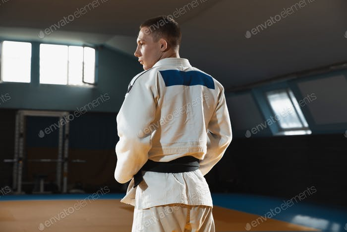 Young judo fighter in kimono posing comfident in the gym, strong and healthy