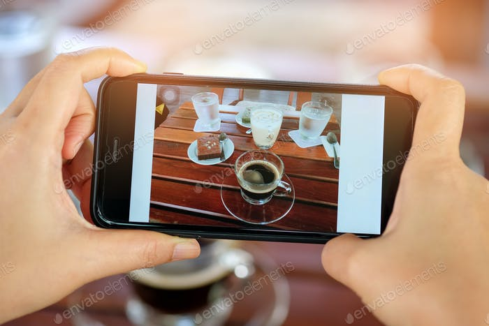 Smartphone in hand with coffee and cake on table.
