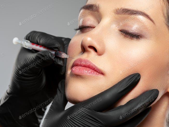 Kaukasische Frau immer Botox kosmetische Injektion in die Lippen. Frau bekommt botox Injektion in Ihr Gesicht