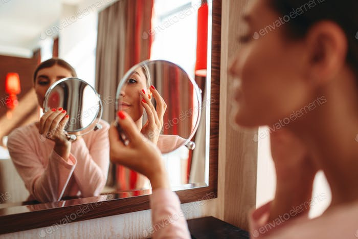 Woman doing makeup at the mirror, face hygiene