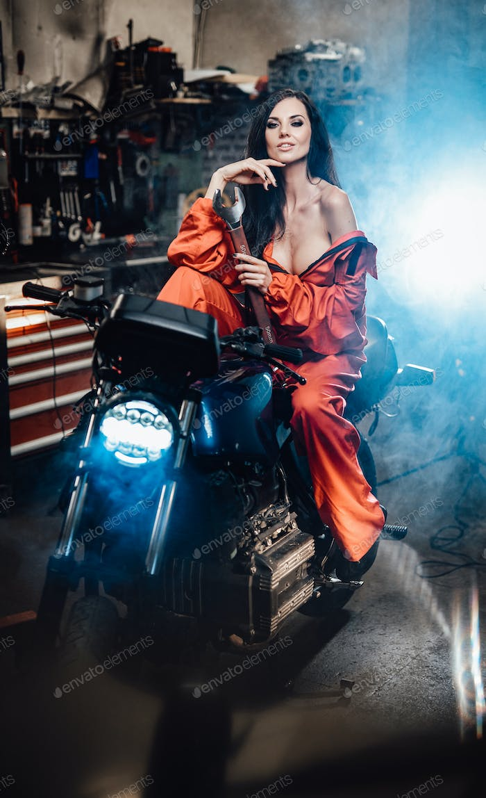 Erotically dressed brunette on a black motorcycle