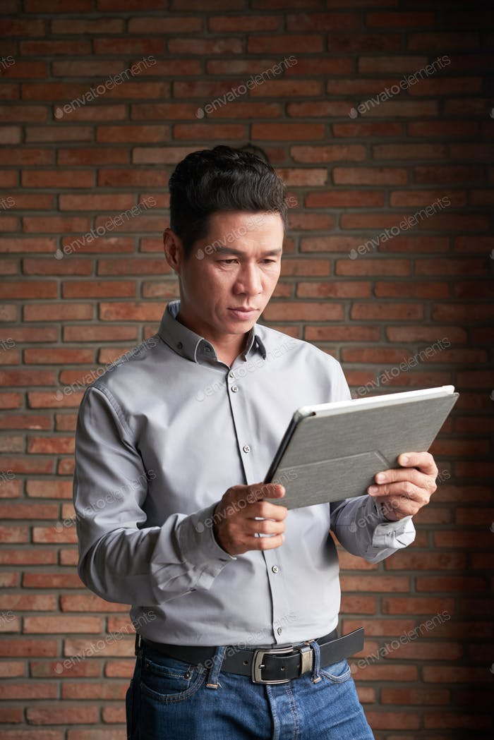 Confident Entrepreneur Using Digital Tablet