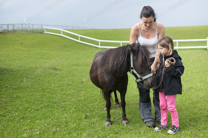 Mother and daughter (4-5) standing with pony