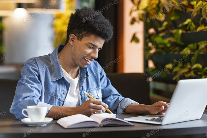 Successful african student working on project at cafeteria