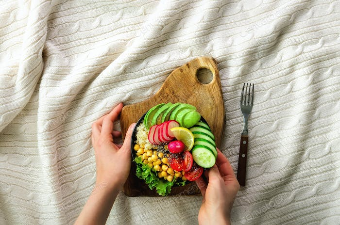 Girl in white jeans holds in hands fork, vegan breakfast meal in bowl with avocado, quinoa, cucumber