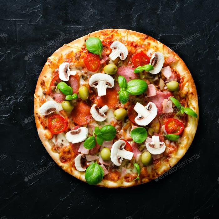 Fresh italian pizza with mushrooms, ham, tomatoes, cheese on on black concrete background. Copy
