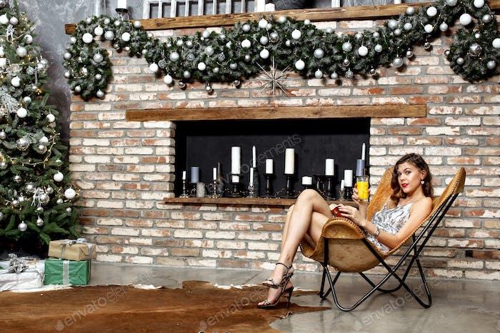 Brünette Mädchen in einem leuchtenden grauen Abendkleid hält ein Glas Saft sitzt in einem Designer