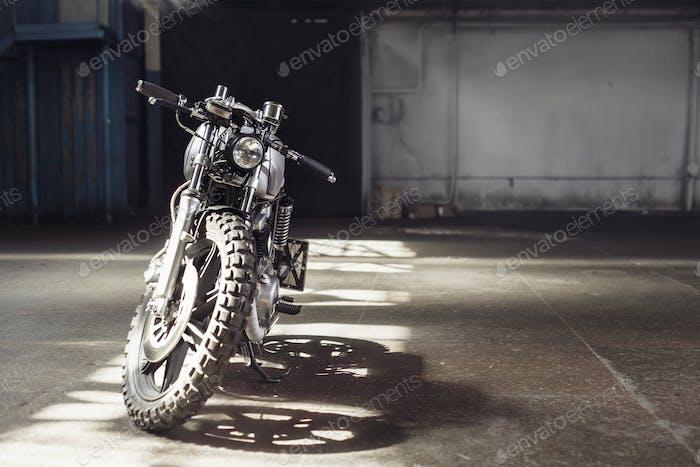 Motorrad im dunklen Gebäude in Strahlen des Sonnenlichts