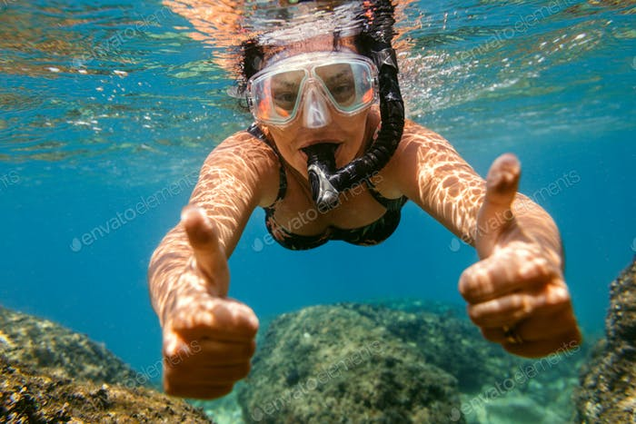 Woman snorkelling under water.
