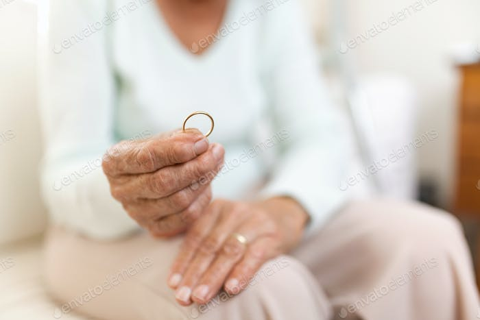 Heartbroken elderly woman holding a wedding ring