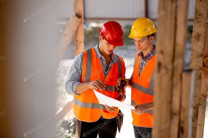 Two men dressed in shirts, orange work vests and helmets explore construction documentation on the