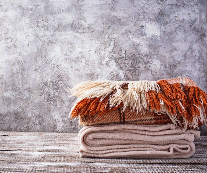 Stack of plaids on light wooden background