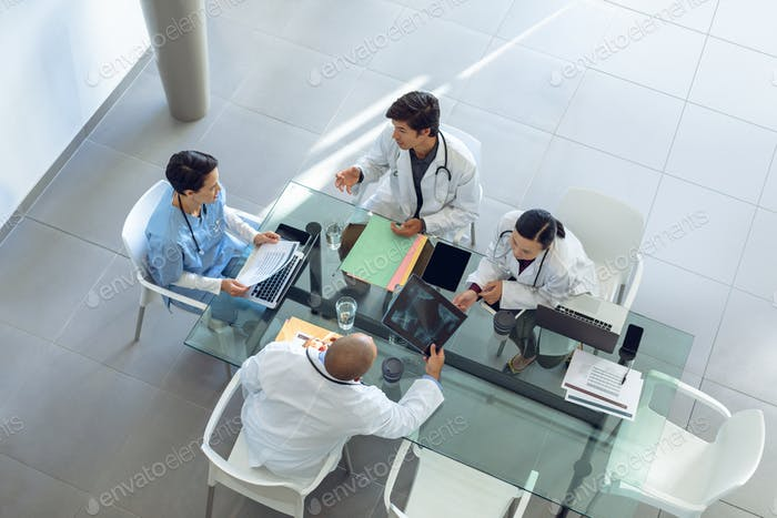 Diverse medical team discussing with each other at the table of conference room in hospital